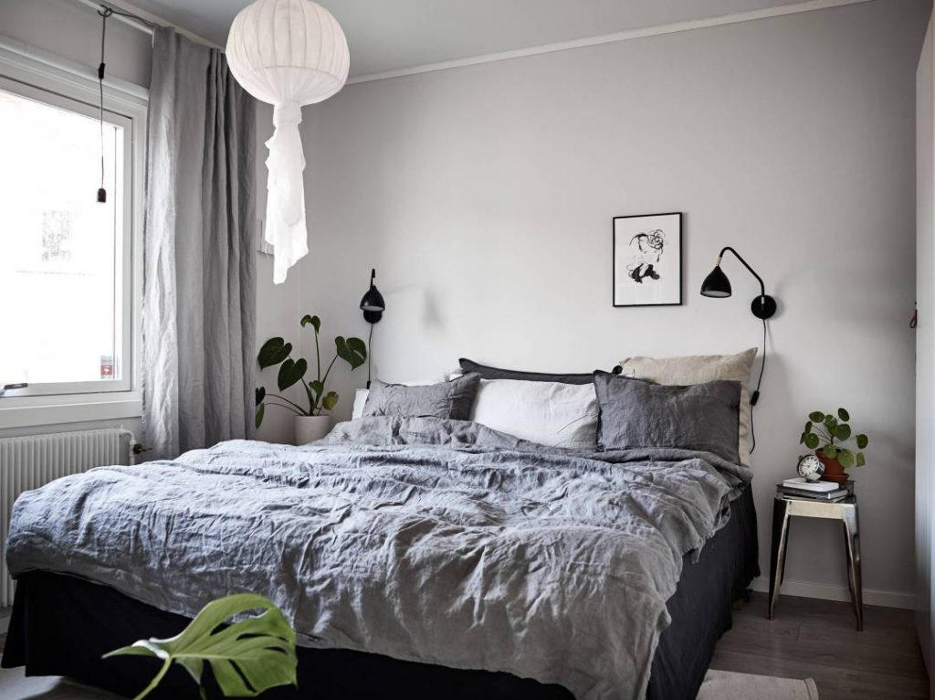 A little rumpled linen lends a warm, inviting vibe to this light blue and white Scandinavian style bedroom