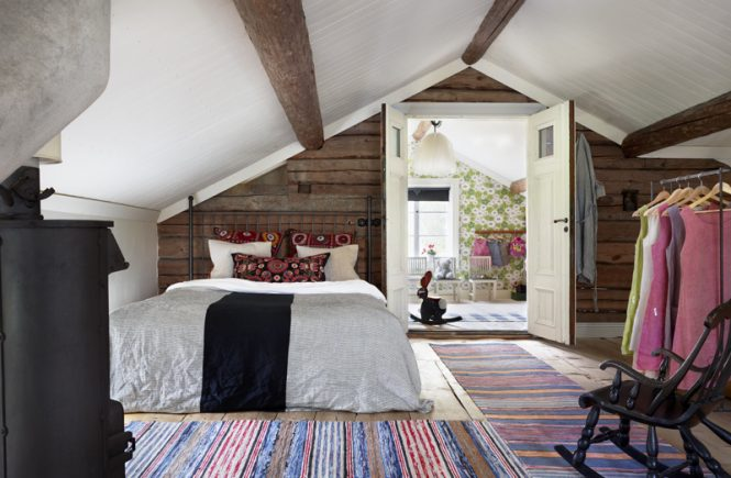 Rustic Swedish attic bedroom with rag rugs.