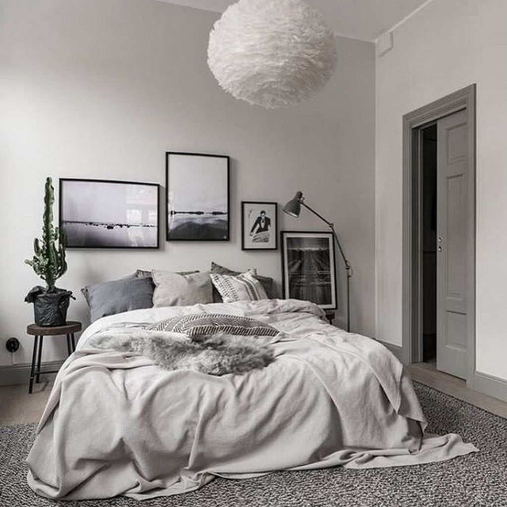 Textured pendant light, rug and pillows in grey bedroom.